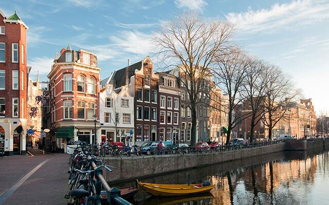 Bomen en grachtenpanden op een zonnige winterdag in Amsterdam