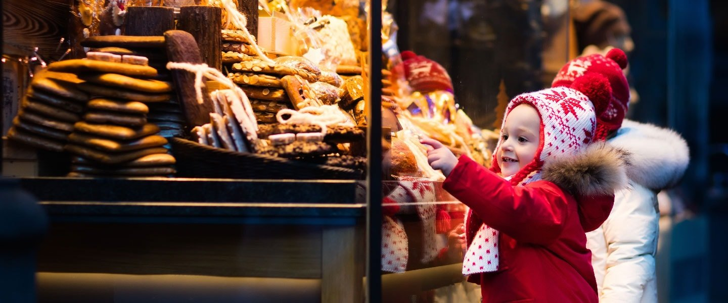 Children looking at gingerbread at other typical German delicacies