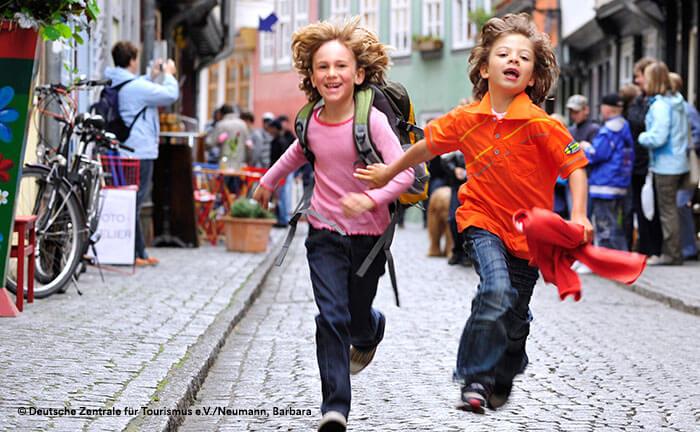 Garçons en train de courir dans ville allemande