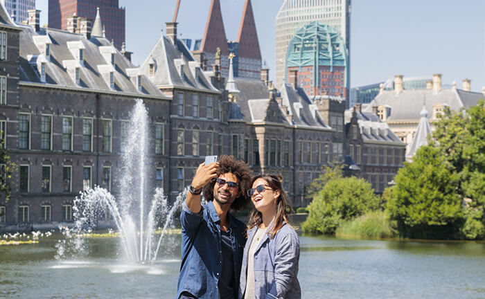 Man and woman taking a selfie in front of the Binnenhof in The Hague